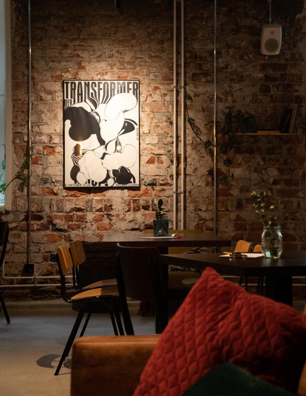 Ravintolan pöytä ja sohva, sohvatyynyjä. Tiiliseinällä mustavalkoinen juliste kehyksissä.