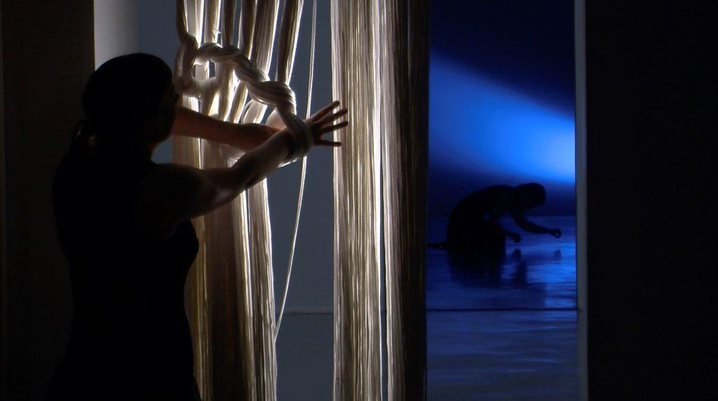 Verho on solmiutunut henkilön käsiin. Taustalla toinen henkilö polvistuneena siluettina sinisessä valossa.