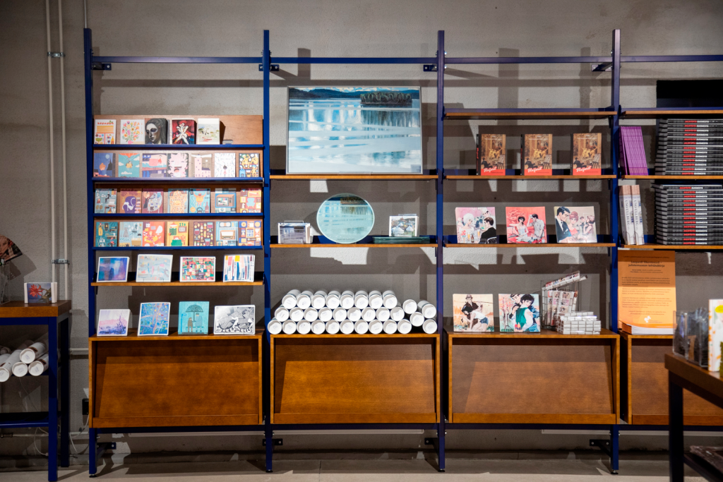 Museokaupan lattiasta korkealle seinään ulottuva hylly, jossa paljon tuotteita: Postikortteja, koristelautanen taidekuvalla ja kirjoja.