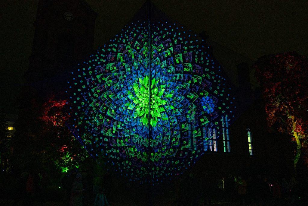 Ornamenttimainen riikinkukon sulkia tai kukkaa muistuttava pyöreähkö valotaideteos vihreän ja sinisen sävyissä.