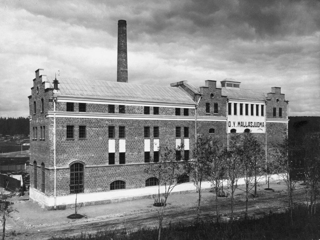 Vanha Mallasjuoman tehdaskiinteistö. Tiilirakennus tien varrella. Taustalla tehtaanpiippu.