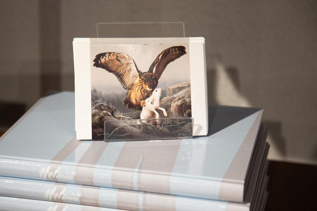 Korttiteline kirjapinon päällä. Kortin kuvassa lentävä petolintu nappaa jäniksen saaliikseen.