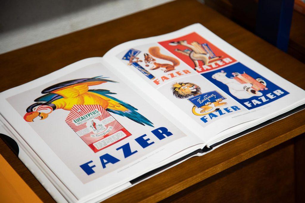Avonainen kirja, jossa kuvia eläinaiheisista Fazerin makeisia markkinoivista julisteista. Papukaija karkkirasian päällä. Leijona pitelemässä suklaalevyä. Jääkarhu, Orava.