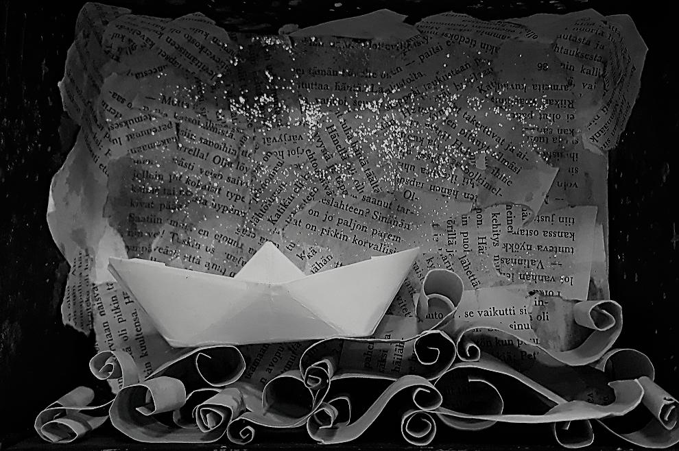 Pahvista ja kirjan sivuista askarreltu merimaisema, jossa vene seilaa.