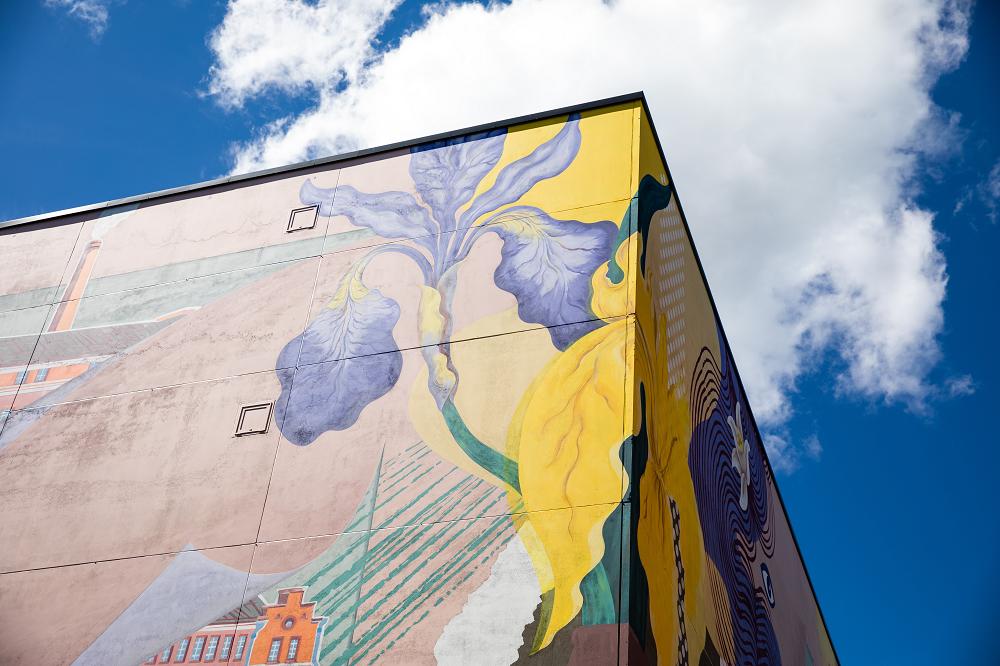 Värikäs Block Party -muraali Malskilla sinistä taivasta vasten.