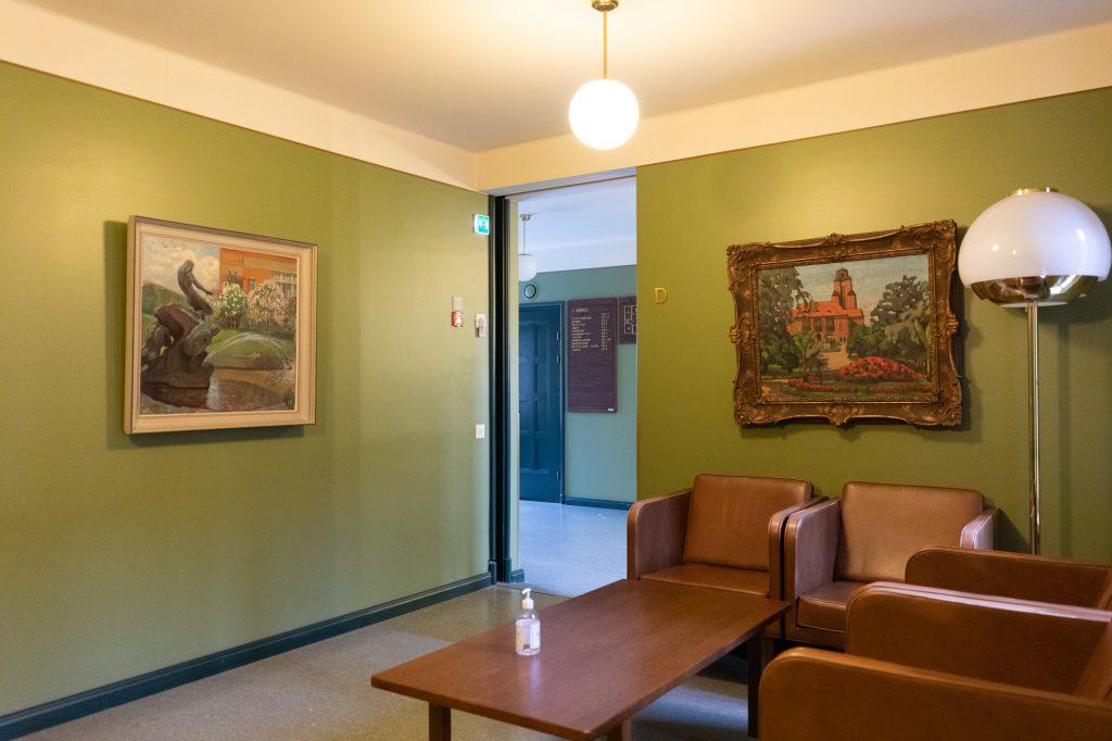 Odotusaula, jonka seinällä kaksi kehystettyä taideteosta.
