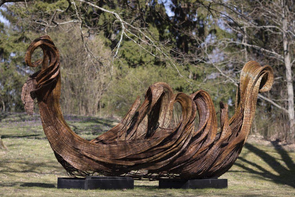 Pajusta ja teräksestä tehty veistos, joka muistuttaa koristeellista kaarnalaivaa.