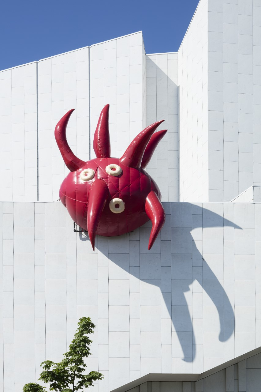 Punaista hedelmää muistuttava pyöreä veistos talon katolla.