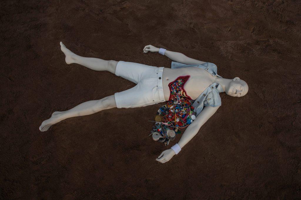 Veistos. Valkoisiin sortseihin puetun selällään makaavan mallinuken vatsasta pursuaa muoviroskaa.