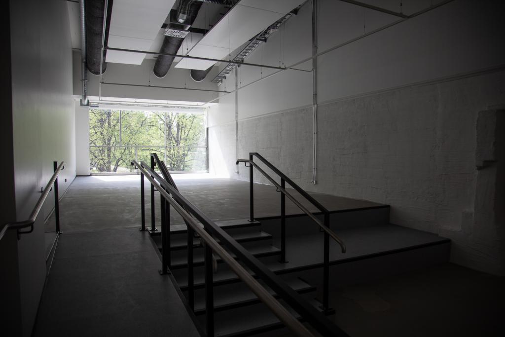 Tyhjä huone, jonka etualalla ramppi ja portaat. Takaseinällä suuri ikkuna, josta näkyy puisto.