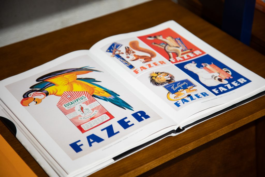 An open book with pictures of posters advertising Fazer confectionery. A parrot on top of a candy box. A lion holding a bar of chocolate. A polar bear and a squirrel.